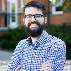 a man with brown hair and beard wearing black glasses and a blue checked shirt