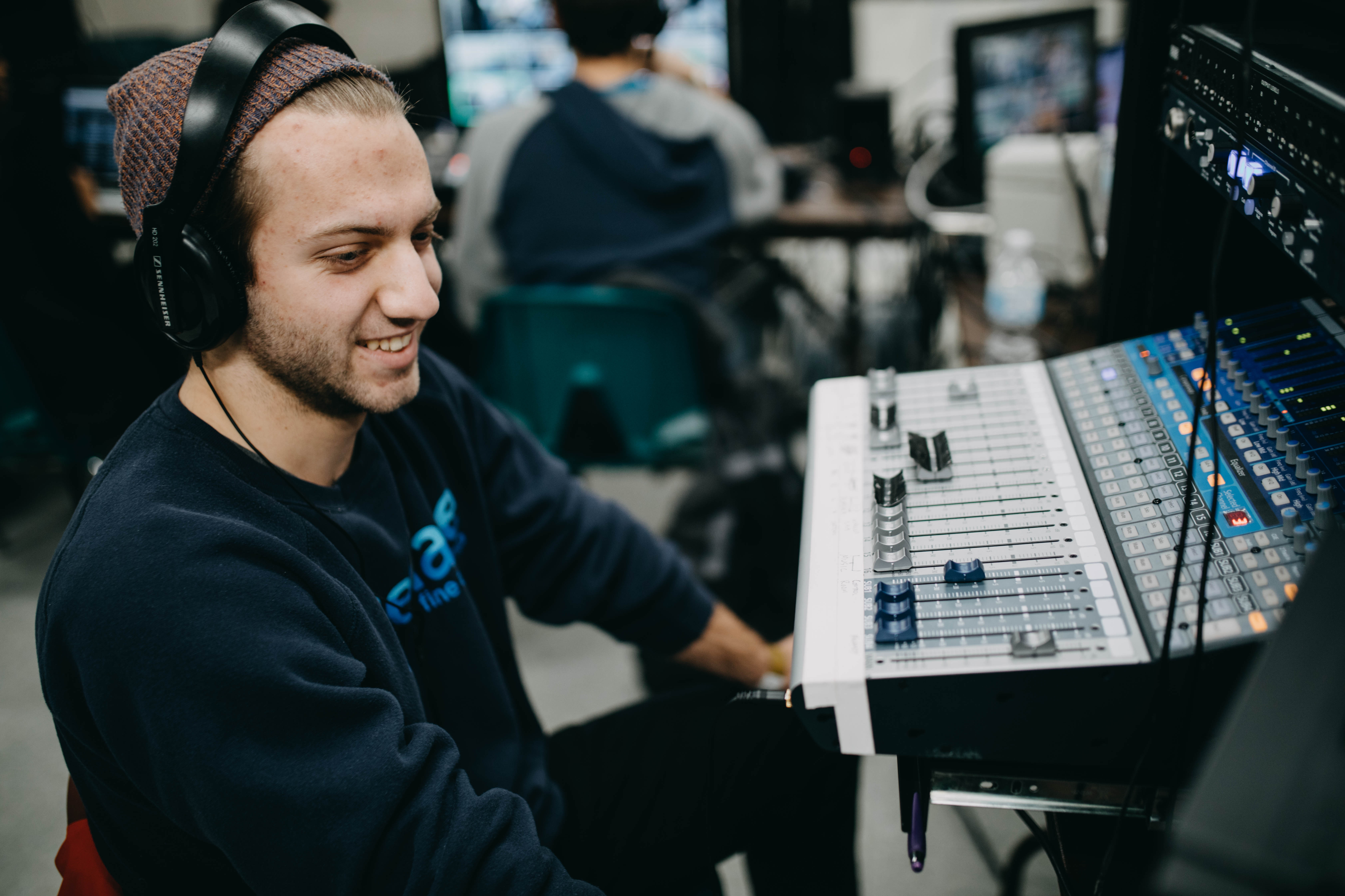 Man smiling as he works on a soundboard