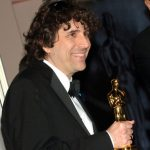 Man wearing suit and tie holding an Oscar statuette