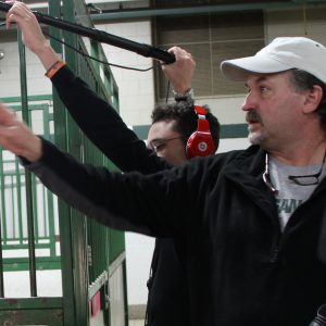 two people by an animal cage with a microphone