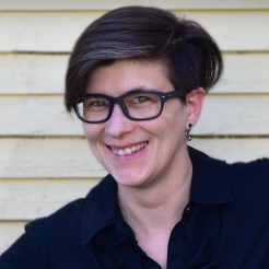 Woman with short hair and glasses wearing a black shirt