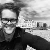 Black and white photo of a man with short hair and thick glasses on the beach
