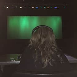 Woman with long hair seen from the back wearing headphones