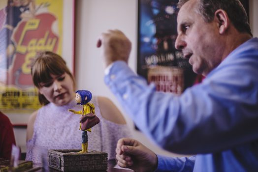 two people look at a clay figurine of Coraline