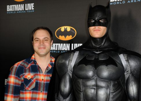 a man in a plaid shirt stands next to a man dressed as Batman