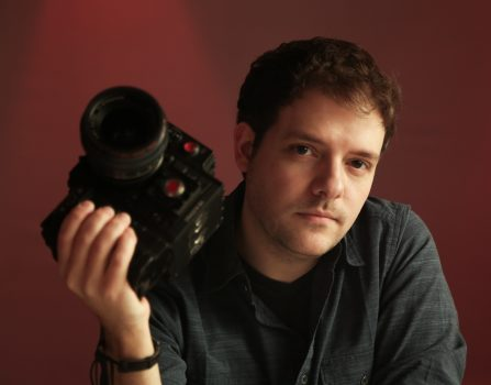 Man with short brown hair holding a camera and posing for a photo